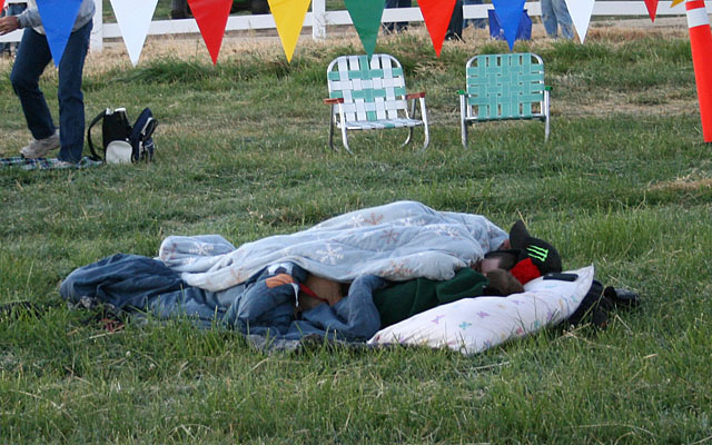 There are people who prefer spending the night at the launch site rathe than getting up at 4:00 am. Under the blanket is a young couple, a child, and a puppy.
